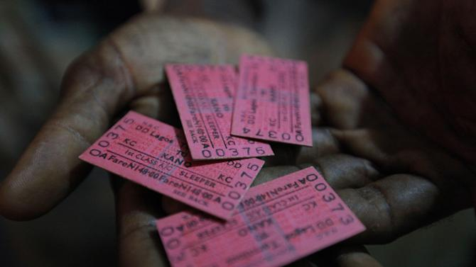 In this Photo taken, Friday, March . 8, 2013, a man displays train tickets to Kano, in Lagos, Nigeria. Nigeria reopened its train line to the north Dec. 21, marking the end of a $166 million project to rebuild portions of the abandoned line washed out years earlier. The state-owned China Civil Engineering Construction Corp. rebuilt the southern portion of the line, while a Nigerian company handled the rest. The rebirth of the lines constitutes a major economic relief to the poor who want to travel in a country where most earn less than $1 a day. Airline tickets remain out of the reach of many and journeys over the nation's crumbling road network can be dangerous. The cheapest train ticket available costs only $13.   ( AP Photo/Sunday Alamba)