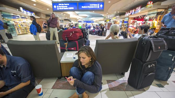 Julie Saso, of San Jose, waits with hundreds of of other travelers at Phoenix Sky Harbor International Airport's terminal 4 wait for police to search for an armed suspect, Thursday, Sept. 18, 2014. The suspect is believed to be involved in a Tempe shooting. Saso just arrived to surprise her niece on her 8th birthday. (AP Photo/The Arizona Republic, Charlie Leight)