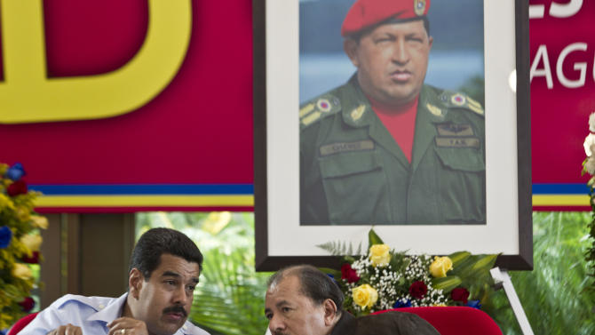 FILE - In this June 29, 2013 file photo, under a portrait of the late Hugo Chavez, Venezuela's President Nicolas Maduro, left, talks with Nicaragua's President Daniel Ortega during the 8th Petrocaribe Summit in Managua, Nicaragua. Chavez's dream of leveraging Venezuela's oil wealth to spread revolution across Latin America is crumbling under the weight of an economic crisis that has forced his hand-picked successor to cut back on generous foreign aid. (AP Photo/Esteban Felix, File)