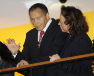 Boxing great Muhammad Ali, with his wife, Lonnie, right, waves to friends attending a celebration for his 70th birthday at the Muhammad Ali Center on Saturday, Jan. 14, 2012, in Louisville, Ky. Ali turns 70 Tuesday. (AP Photo/Mark Humphrey)