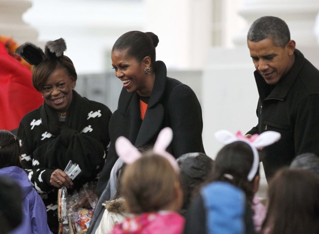 President Barack Obama, right, first lady Michelle Obama, center, her mother Marian Robinson, left, hand out Halloween treats as they welcome children from the Washington area and military members and