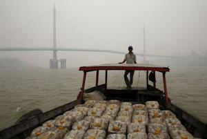 A man stands on his wooden boat as it crosses the haze…