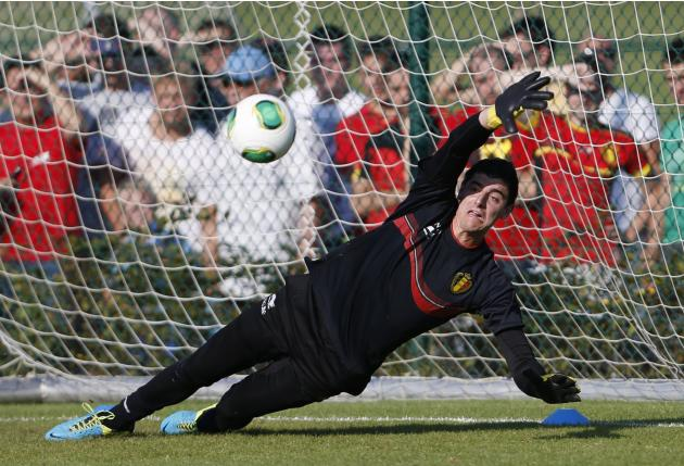 Belgian national soccer team goalkeeper Courtois dives for the ball during a training session in Brussels