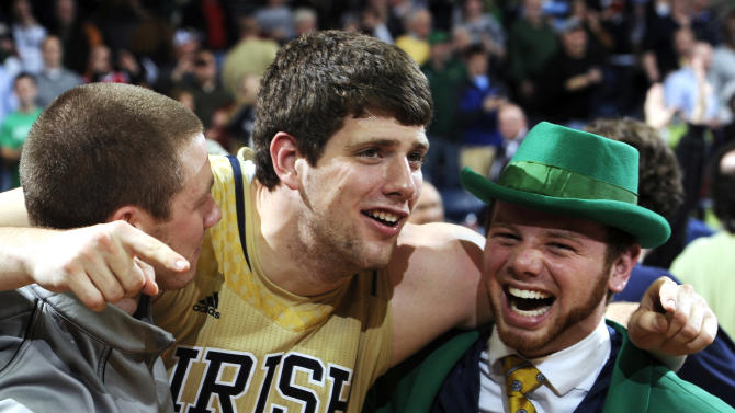 Notre Dame forward Tom Knight (25) celebrates with Leprechaun Bryce Burton following an NCAA college basketball game against Louisville, Saturday, Feb. 9, 2013, in South Bend, Ind. Notre Dame won 104-101 in five overtimes. (AP Photo/Joe Raymond)