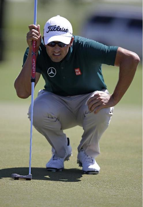 Adam Scott, of Australia, looks over his line on the second green during the third round of the Cadillac Championship golf tournament Saturday, March 8, 2014, in Doral, Fla