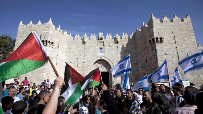 FILE - In this May 8, 2013 file photo Israelis and Palestinians wave flags as Israelis march celebrating Jerusalem Day outside Damascus Gate in Jerusalem's old city. The U.S. on Sunday, July 29 announced the resumption of Israeli-Palestinian talks following years of stalemate, after Israel's Cabinet agreed to release 104 Palestinian prisoners convicted of deadly attacks. The return to direct contacts between the sides gave U.S. Secretary of State John Kerry his first concrete achievement after months of shuttle diplomacy. (AP Photo/Sebastian Scheiner, File)