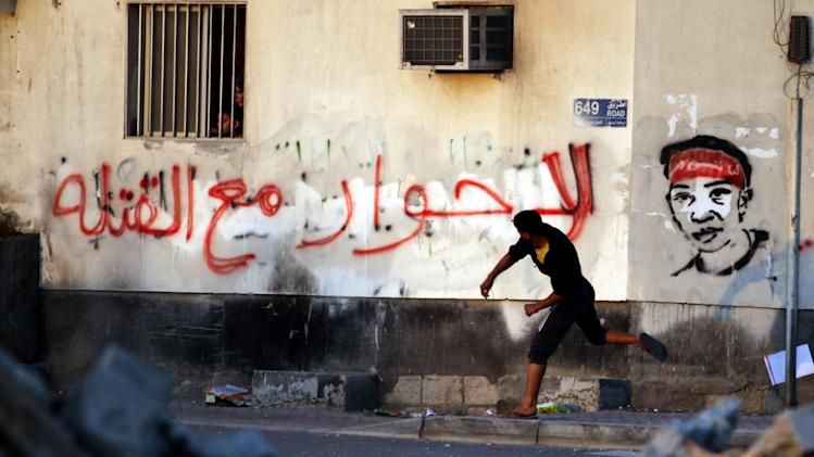 "A woman and her child watch clashes between anti-government protesters and riot police from their window as a protester hurls a stone toward police in Sitra, Bahrain, on Wednesday, Feb. 13, 2013. Clashes erupted in several opposition villages around the kingdom on the eve of the second anniversary of a pro-democracy uprising. Graffiti on the wall reads: ""No to dialogue with murderers."" (AP Photo/Hasan Jamali)"