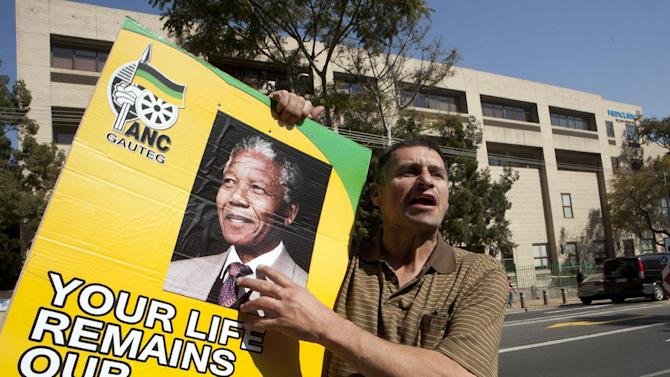 A man only known as Kobus, holds a ruling party poster with former South African President Nelson Mandela's face outside the Mediclinic Heart Hospital where he is being treated in Pretoria, South Africa Wednesday, July 17, 2013. (AP Photo/Themba Hadebe)