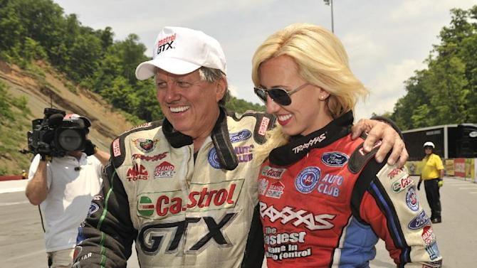 In this photo provided by NHRA, Funny Car driver John Force celebrates his victory with daughter and Funny Car driver Courtney Force, Sunday, June 16, 2013, at the Ford NHRA Thunder Valley Nationals in Bristol, Tenn. Force, a 15-time Funny Car world champion, picked up his first win of 2013 in his Castrol GTX Ford Mustang and fourth at legendary Bristol Dragway, defeating Cruz Pedregon in the final. John Force also knocked off Courtney in the first round of eliminations on Sunday en route to the victory, which ended a 31-race winless streak and is the 135th of his career. (AP Photo/NHRA, Teresa Long)