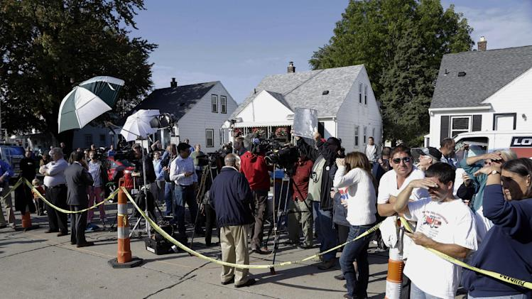 Media and spectators watch as authorities drill for soil samples in the floor at a Roseville, Mich., home Friday, Sept. 28, 2012. Police have been told by a source that former Teamsters boss Jimmy Hoffa may be buried beneath a driveway. (AP Photo/Paul Sancya)