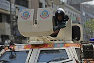 A Bangladeshi policeman stands guard on an armored car during a nationwide strike in Dhaka last week. The opposition Bangladesh Nationalist Party accuse the elite Rapid Action Battalion security force of abducting Ilias Ali, an allegation both the force and the government have rejected