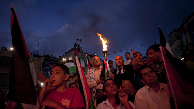 Palestinians wait moments before their President Mahmoud Abbas addressed the General Assembly of the United Nations, in the West Bank city of Ramallah, Friday, Sept. 23, 2011. (AP Photo/Bernat Armangue)