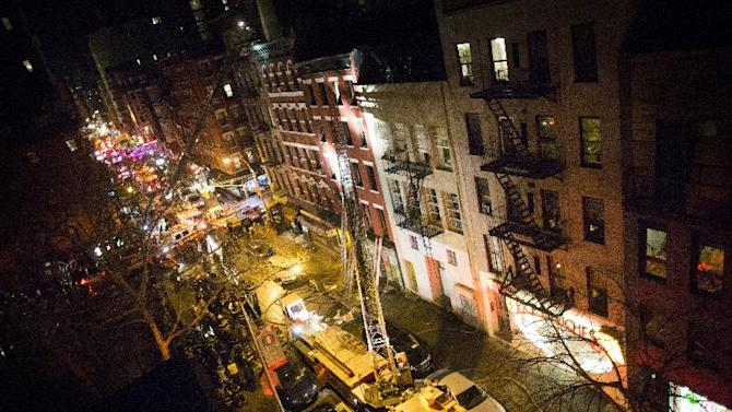 Fire trucks stretch for blocks after a five alarm fire at 41 Spring Street in lower Manhattan burned through the building, Thursday, Jan. 10, 2013, in New York. One woman was killed. (AP Photo/John Minchillo)