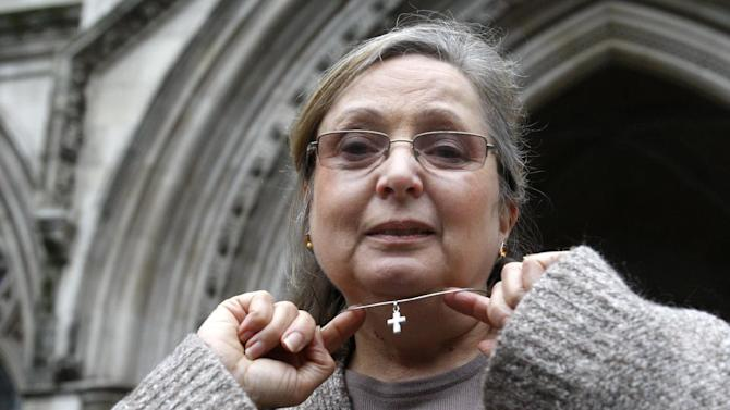 FILE - This is a Tuesday, Jan. 19, 2010. file photo  of  British Airways check-in employee Nadia Eweida, shows her Christian cross to the media, as she arrives at the Royal Courts of Justice to fight a ruling that she was not a victim of religious discrimination by British Airways.  British Airways discriminated against Eweida a devoutly Christian airline employee by making her remove a crucifix at work, Europe's highest court ruled Tuesday Jan. 15, 2013 . But the court rejected discrimination cases by three other Christian claimants. Nadia Eweida sparked a national debate in Britain over religion in public life when she was sent home in November 2006 for refusing to comply with rules banning employees from wearing visible religious symbols. (AP Photo/Sang Tan, File)