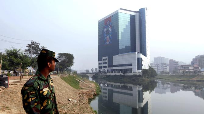 """In this Saturday, Dec. 8, 2012, photo, a Bangladesh Army soldier stands near the headquarters of the Bangladesh Garment Manufacturers and Export Association (BGMEA) in Dhaka, Bangladesh. About a year before a November fire at a clothing factory in Bangladesh killed 112 people, executives from Wal-Mart, Gap and other big clothing companies met nearby in the country's capital to discuss a legally binding contract that would govern safety inspections. But after a spokeswoman for Wal-Mart, the world's largest retailer, got up and said the proposal wasn't """"financially feasible,"""" the effort quickly lost momentum. (AP Photo/A.M. Ahad)"""
