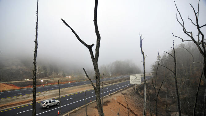 Charred trees are all that stand on the along Interstate 77 Wednesday Dec. 12, 2012, where a gas line ruptured and exploded in Sissonville, W.Va., Tuesday. The interstate pavement melted from the heat of the explosion, shutting down Interstate 77 overnight. But the northbound lanes of the interstate reopened at 8am Wednesday, and the southbound lanes a few hours later. Investigations into what caused the massive blast in a 20-inch Columbia Gas Transmission line are under way.  (AP Photo/Charleston Daily Mail,Tom Hindman)