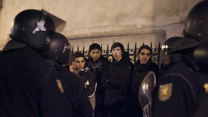 """Demonstrators are held by riot police officers following a protest in Madrid, Spain, Sunday, Feb. 24, 2013. Tens of thousands of people marched on Spain's parliament on Saturday to protest austerity measures, a demonstration that came on the 32nd anniversary of a failed attempt by the armed forces to overthrow the government. Protest groups joined forces under the slogan """"Citizens' Tide, 23F,"""" referring to the Feb. 23, 1981, attack by the armed forces on the parliament. (AP Photo/Gabriel Pecot)"""