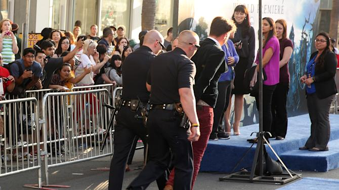"A fan is walked off carpet in handcuffs after allegedly attacking Brad Pitt at the world premiere of ""Maleficent"" at the El Capitan Theatre on Wednesday, May 28, 2014, in Los Angeles. (Photo by Matt Sayles/Invision/AP)"