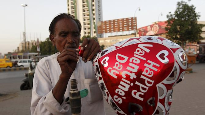 A vendor inflates a heart-shaped balloon from his cart ahead of Valentine's Day along a road in Karachi,