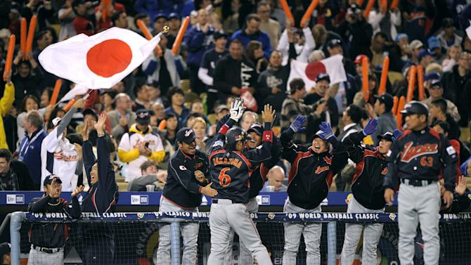 FILEL - In this March 23, 2009 file photo, Japan celebrates on the field after beating South Korea 5-3, in the final of the World Baseball Classic in Los Angeles. The Japanese players' association agreed to take part in the 2013 World Baseball Classic Tuesday, Sept. 4, 2012, backing off from a threat to boycott the event over the way tournament revenue is shared. (AP Photo/Mark J. Terrill, File)