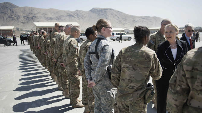 FILE - In this July 7, 2012, file photo, Secretary of State Hillary Rodham Clinton, right, greets troops before departing Kabul International Airport. U.S. troop deaths in Afghanistan have plunged to the lowest level in four years, reflecting a pullback from direct combat into the less deadly role of advising and assisting Afghan forces as they do more of the fighting. Attacks by the Taliban insurgents also have been declining, although the war is far from finished. (AP Photo/Brendan Smialowski, File, Pool)