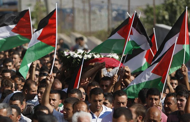 Palestinian mourners carry the body of Akram Badr, 46, during his funeral in the village of Beitillu near in the West Bank city of Ramallah, Tuesday, July 31, 2012. Badr was killed at a checkpoint by the Israeli security forces near Jerusalem Monday (AP Photo/Majdi Mohammed)