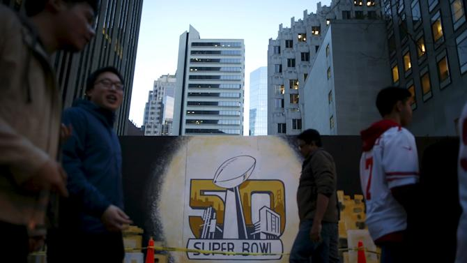 People walk past a mural in downtown San Francisco before NFL Super Bowl 50 in San Francisco