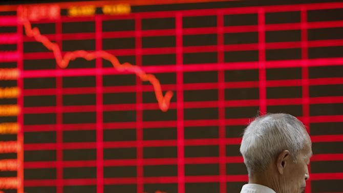 Man is seen in front of  a board showing a graph of stock prices at a brokerage office in Beijing