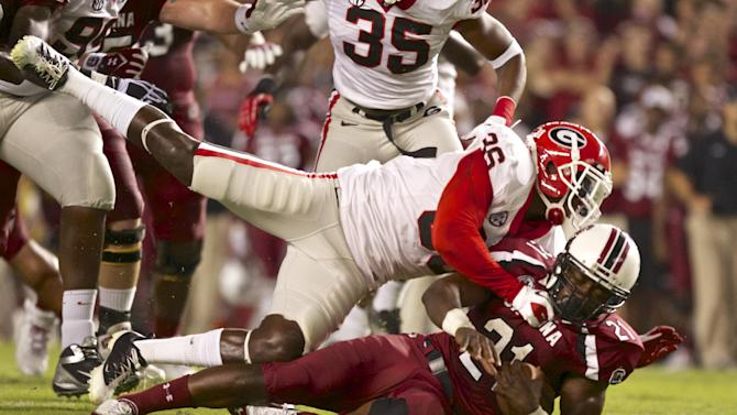 South Carolina running back Marcus Lattimore is tackled by Georgia strong safety Shawn Williams during the first quarter of an NCAA college football game in Columbia, S.C., Saturday, Oct. 6, 2012. (AP Photo/Brett Flashnick)