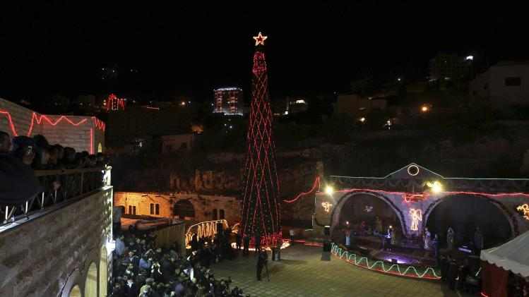 People gather to celebrate the lighting of a Christmas tree in the mostly Christian town of Al-Fuheis