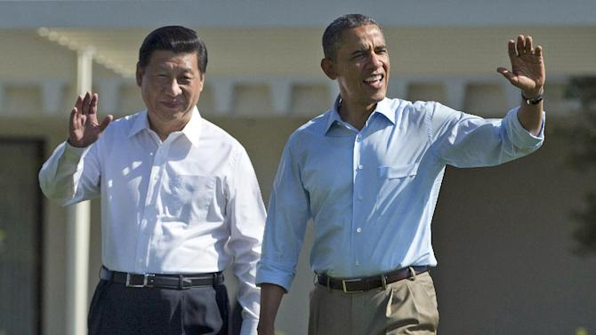 """President Barack Obama and Chinese President Xi Jinping, left, walk at the Annenberg Retreat of the Sunnylands estate Saturday, June 8, 2013, in Rancho Mirage, Calif. While saying it is critical that the U.S. and China reach a """"firm understanding"""" on cyber issues, Obama told reporters his meetings with Xi have been """"terrific."""" (AP Photo/Evan Vucci)"""