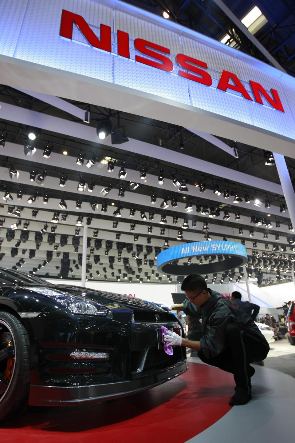 A worker cleans Nissan GT-R at the Beijing International Auto Exhibition in Beijing, China, Monday, April 23, 2012. (AP Photo/ Vincent Thian)