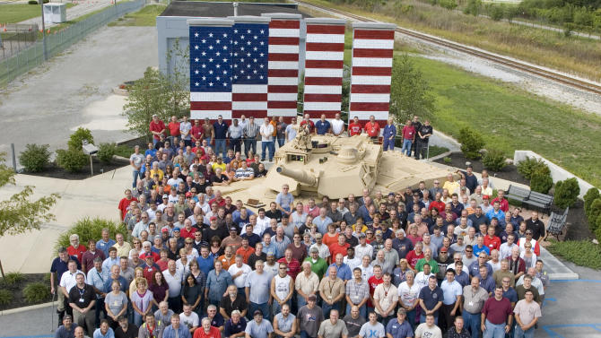 In this undated photo released by General Dynamics Land System workers gather around an Abrams tank outside the plant in Lima, Ohio. Rows of sand-colored armored vehicles ready for deployment are parked outside the nation's only tank manufacturing plant. It's where welders and machinists for more than three decades have built the Abrams tank. But the Pentagon says it will soon have enough tanks and wants to halt production for several years as it wrestles with deep cuts in military spending over the next decade. (AP Photo/HO, General Dynamics Land System)
