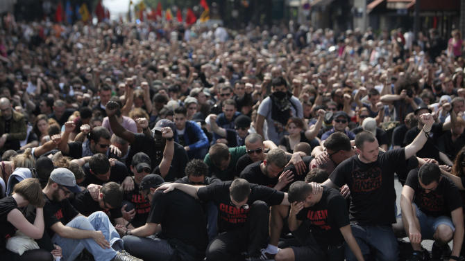 Protestors pay respects to Clement Meric, at a demonstration in honour of Clement Meric, an anti-fascist activist killed in a fight with skinheads in Paris on June 5, in Paris, Saturday, June 8, 2013. The Paris prosecutor said Saturday he is seeking an investigation for murder against a 20-year-old far-right militant suspected of being involved in the killing of an anti-fascist activist in Paris this week. (AP Photo/Thibault Camus)