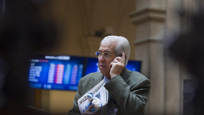"A broker talks on a cell phone at the stock exchange in Madrid, Monday May 7, 2012.  Spain's prime minister says the government will likely present important bank clean-up measures this week to clear up doubts about the solvency of the sector. Rajoy gave no details but said he would not rule out lending or injecting public money into the banking sector if necessary. Spain's real estate bubble burst in 2008 saddling banks with enormous amounts of bad loans. The Bank of Spain says the sector has about 175 billion euros ($230 billion) in ""problematic"" holdings. (AP Photo/Paul White)"