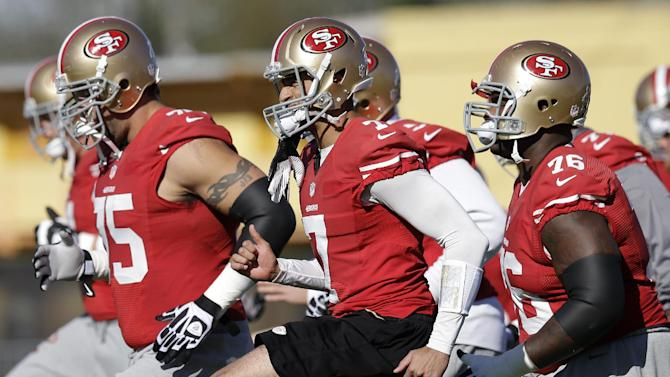 San Francisco 49ers quarterback Colin Kaepernick, center, warms up with guard Alex Boone (75) and tackle Anthony Davis (76) during practice on Thursday, Jan. 31, 2013, in New Orleans. The 49ers are scheduled to play the Baltimore Ravens in the NFL Super Bowl XLVII football game on Feb. 3. (AP Photo/Mark Humphrey)