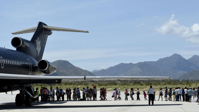 Tourists board a plane at the airport of San Jose del Cabo, on September 16, 2014