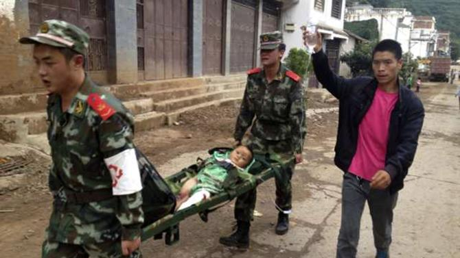 Paramilitary policemen carry an injured child on a stretcher after an earthquake hit Longtoushan township of Ludian county