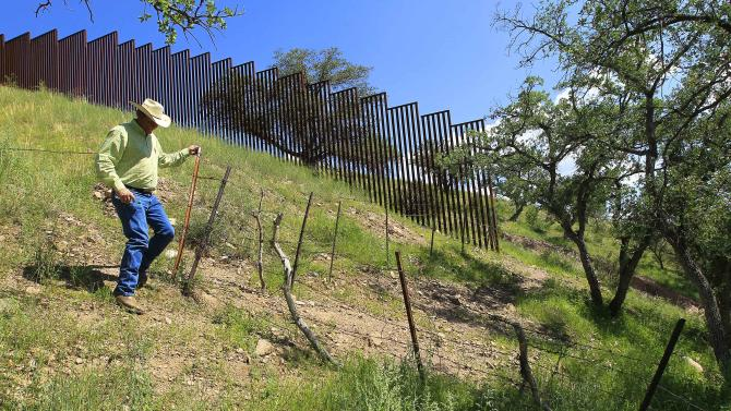 In this Friday, Aug. 10, 2012 photo, rancher Dan Bell, who owns a 35,000-acre cattle ranch along the border between the United States and Mexico, checks out part of his property where the barbed-wire fence is often damaged by illegal border crossers, in Nogales, Ariz. When Bell drives through his property, he speaks of the hurdles that the Border Patrol faces in his rolling green hills of oak and mesquite trees: The hours it takes to drive to some places, the wilderness areas that are generally off-limits to motorized vehicles, and the environmental reviews required to extend a dirt road. (AP Photo/Ross D. Franklin)