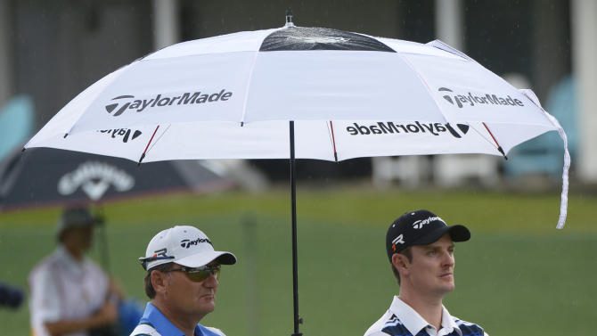 Caddie Terry Mundy, left, holds an umbrella over Justin Rose as rain falls while Rose waits to hit on the 16th fairway during the second round of the Arnold Palmer Invitational golf tournament in Orlando, Fla., Friday, March 22, 2013. (AP Photo/Phelan M. Ebenhack)