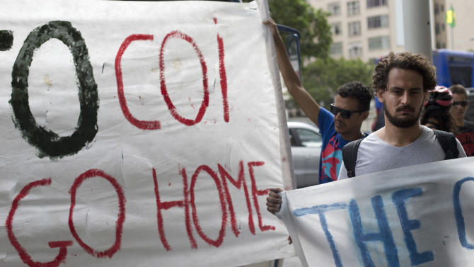 "Protesters hold a banner that reads: ""COI go home,"" at the entrance of the hotel where International Olympic Committee meeting in Rio de Janeiro, Brazil, Saturday, Feb. 28, 2015. Golf's return to the Olympics after a more than century-long absence was meant to be triumphal, but the construction of the course in the Marapendi nature reserve, a narrow strip of green in the heart of one of Rio's fastest-growing neighborhoods, has been dogged by legal wrangling and protests by Environmental activists. (AP Photo/Silvia Izquierdo)"