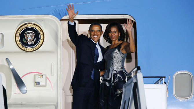 US President Barack Obama and first lady Michelle Obama wave goodbye from Air Force One at the Tegel airport in Berlin Wednesday, June 19, 2013. Obama was for a two-day official visit to Germany. (AP Photo/Michael Probst)