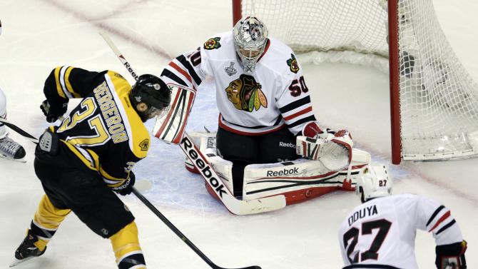 Boston Bruins center Patrice Bergeron (37) moves the puck between Chicago Blackhawks goalie Corey Crawford (50) and defenseman Johnny Oduya (27), of Sweden, during the first period in Game 3 of the NHL hockey Stanley Cup Finals in Boston, Monday, June 17, 2013. (AP Photo/Charles Krupa)