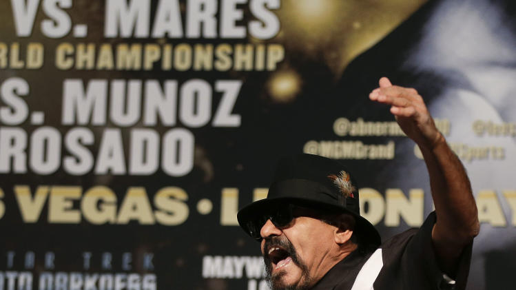 Ruben Guerrero, right, father of fighter Robert Guerrero, left, shouts at Floyd Mayweather Jr. calling him a wife beater during a news conference, Wednesday, May 1, 2013, in Las Vegas. Robert Guerrero will challenge Mayweather for Mayweather's WBC welterweight title on Saturday. (AP Photo/Julie Jacobson)