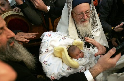 <p>A rabbi carries an eight-day-old baby during a 2004 circumcision ceremony in Jerusalem. Circumcising young boys on religious grounds amounts to grievous bodily harm, a German court ruled Tuesday in a landmark decision that the Jewish community said trampled on parents' religious rights.</p>
