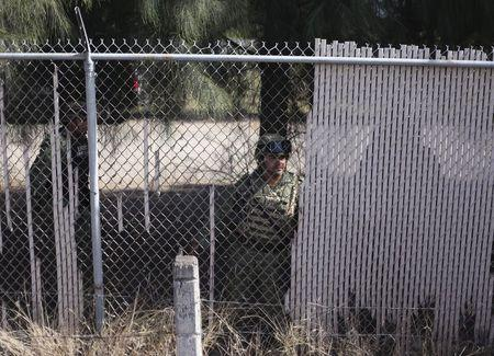 Soldiers keep watch behind the fence of a ranch where a gunfight between hitmen and federal forces left several casualties in Tanhuato