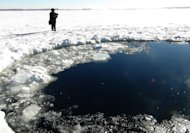 A police officer looks at a hole in a lake near Chebakul in Russia's Chelyabinsk region yesterday. Divers scoured the bottom of a Russian lake on Saturday for fragments of a meteorite that plunged to Earth in a blinding fireball whose shockwave injured 1,200 people and damaged thousands of homes