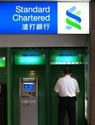 A man uses a Standard Chartered bank cash machine in Hong Kong, August 4. Standard Chartered has settled allegations that it helped Iranian clients dodge US sanctions, announcing a fine of $340 million from a New York banking watchdog