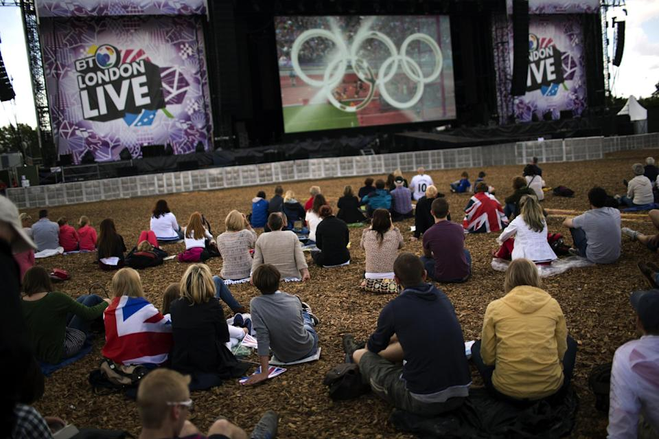 In this Monday, Aug. 6, 2012 photo, people watch a broadcast of the woman's 1500-meter semifinals on a screen at Hyde Park in London during 2012 Summer Olympics, in London. (AP Photo/Emilio Morenatti)