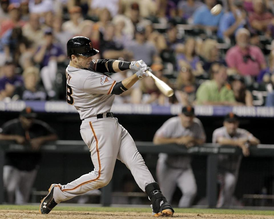 San Francisco Giants' Buster Posey hits a solo home run in the ninth inning against the Colorado Rockies during a baseball game in Denver on Friday, June 28, 2013. The Rockies won 4-1. (AP Photo/Joe Mahoney)